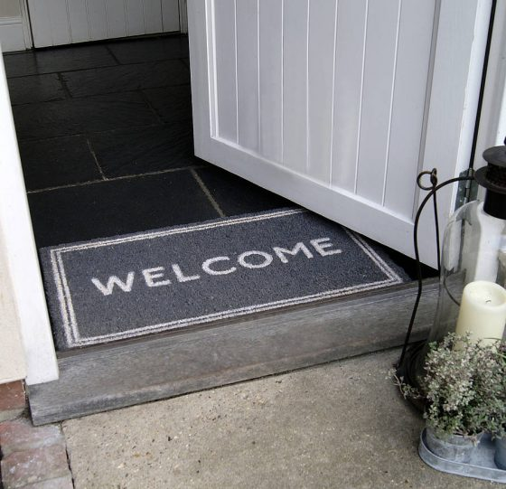 Grey-welcome-mat-with-written-welcome-sign-on-it
